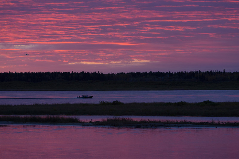Sky before sunrise over the Moose River at Moosonee. Taxi boat headed to Moose Factory.