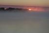 Sunrise on a foggy morning. Barges enshrouded in fog.
