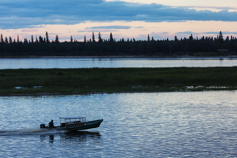 Canoe coming to Moosonee as clouds move in. Little colour in sky.
