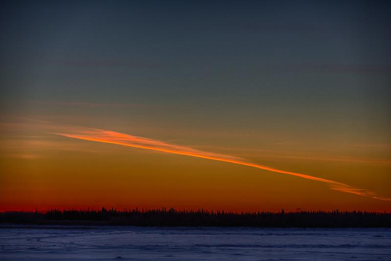Streak off clouds angled in the sky across the Moose River from Moosonee before sunrise. HDR Efx Dark