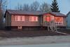 44 Revillon Road before sunrise; its windows reflect the sky.
