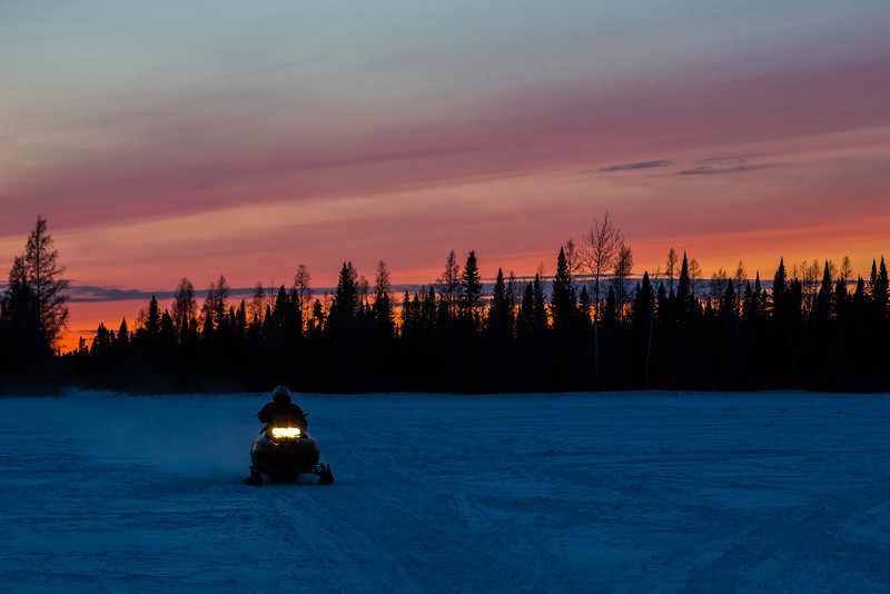 Sunset at Moosonee. Snowmobile coming along a trail that runs into the winter road and Butcher Street.
