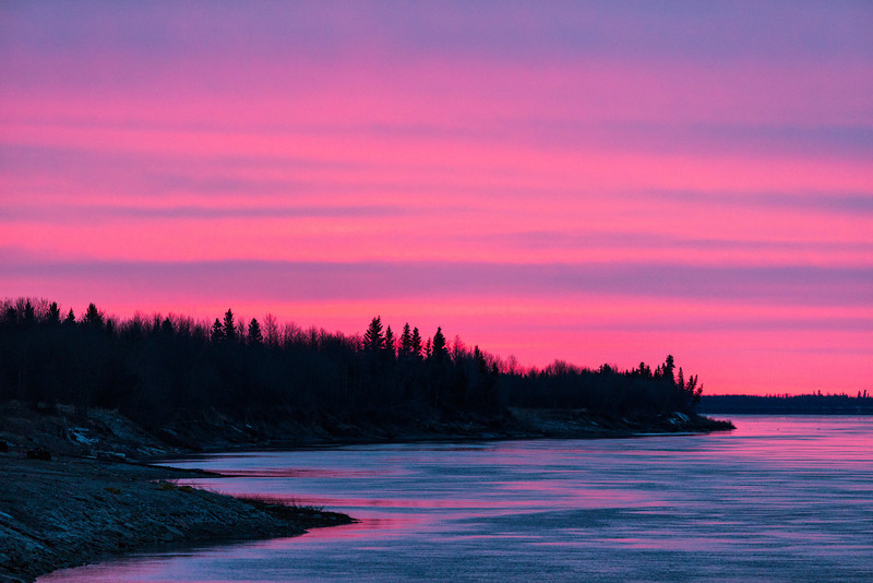 Colour traces shoreline. Looking down the Moose River from Moosonee before sunrise. Clouds over thin streak of colour.