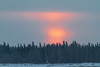 Sunrise through the clouds looking across the Moose River from Moosonee.