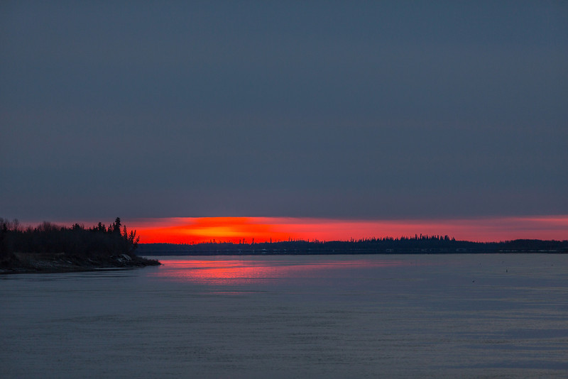 After sunrise down the Moose River at Moosonee. Sun climbing up into the clouds.