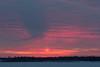 Looking across the Moose River at Moosonee before sunrise. Dark finger jutting into clouds.