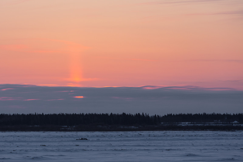 Sunrise across the Moose River from Moosonee with clouds along the horizon.
