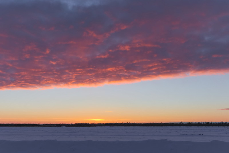 Sky before the horizon; very bright area just above horizon; open sky then fluffy pink clouds above.