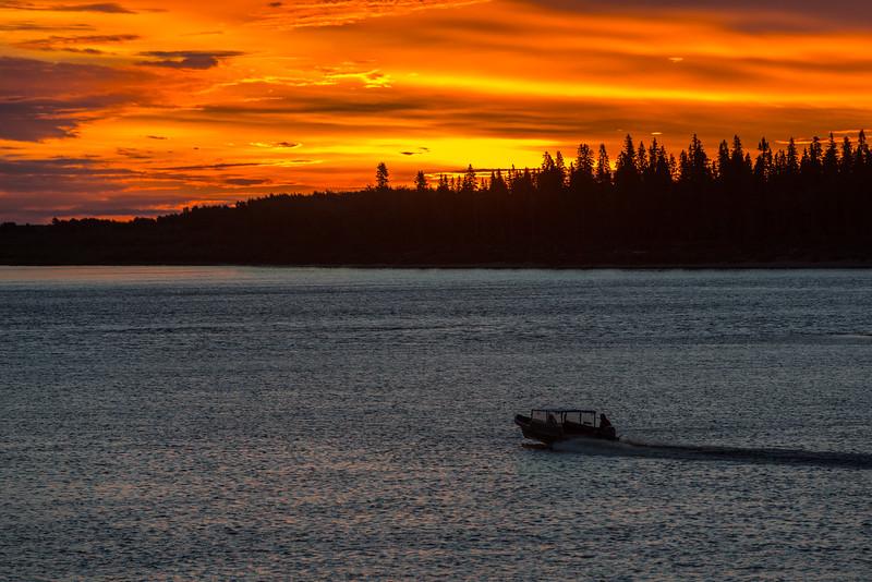 Sky before sunrise over the Moose River at Moosonee. Canoe heading to Moose Factory.