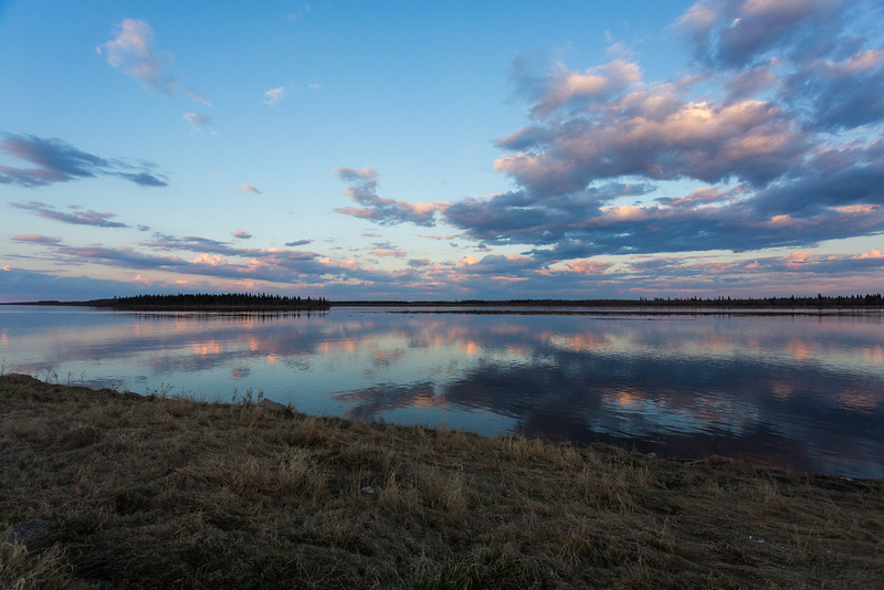 Mirrored clouds over the Moose River at Moosonee.