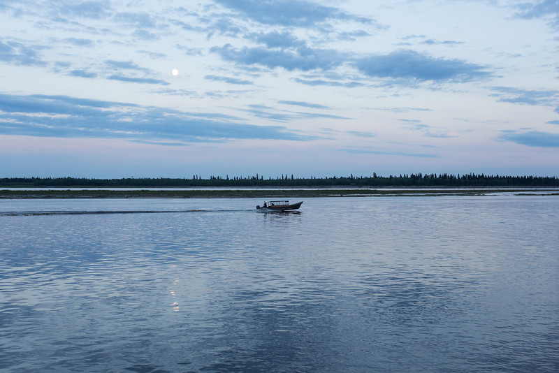 Clouds over the Moose River around sunset. Taxi boat goes past reflection of the moon in the water. Distance bird cloned out of picture.