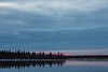 South end of Butler Island at sunrise on the Moose River at Moosonee. Some red colour low in the otherwise dark sky. Dark spot in centre of image is bird.