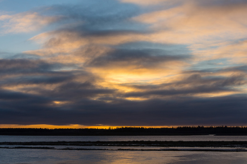 Cloudy skies after sunrise, looking across the Moose River from Moosonee.
