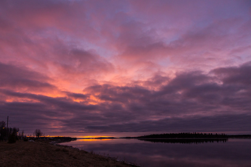 Lookig down the Moose River before sunrise at Moosonee. A bit of colour along the horizon, dark clouds with hints of colour above below half open sky.