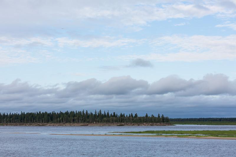 Darker low lying clouds pass over the Moose River at Moosonee, Ontario.