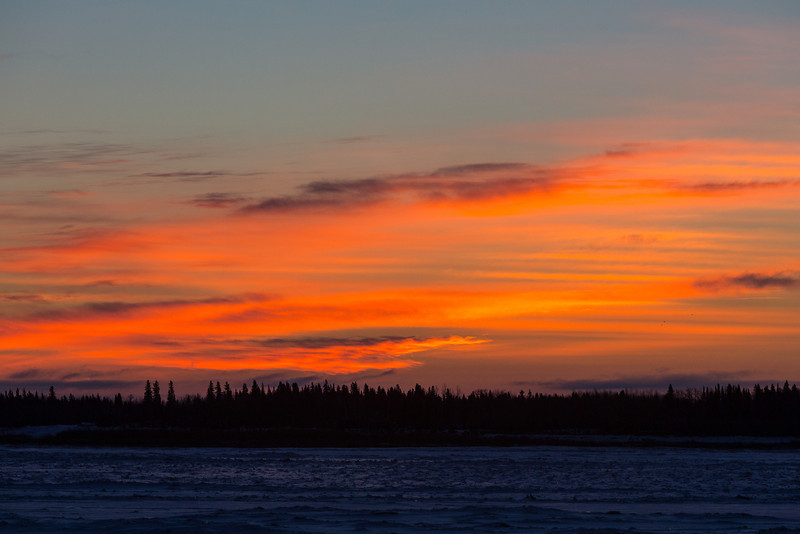 Clouds across the Moose River from Moosonee lit up before sunrise.