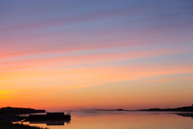 Sky before sunrise looking down the Moose River past barge docks.