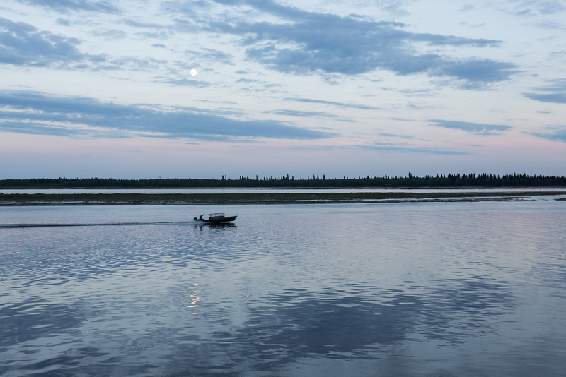 Clouds over the Moose River around sunset. Moon reflected in the water as boat goes by.