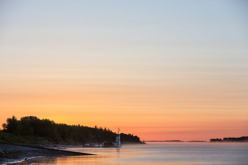 Wider view looking down the Moose River at Moosonee at sunrise. Sun has yet to appear over the trees.
