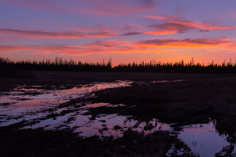 Clouds over boggy ground on far side of tracks in Moosonee at sunset. HDR from three exposures.