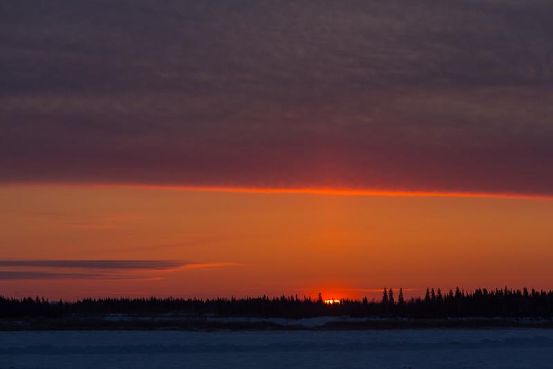 Sunrise at Moosonee looking across the Moose River. High clouds gain colour.