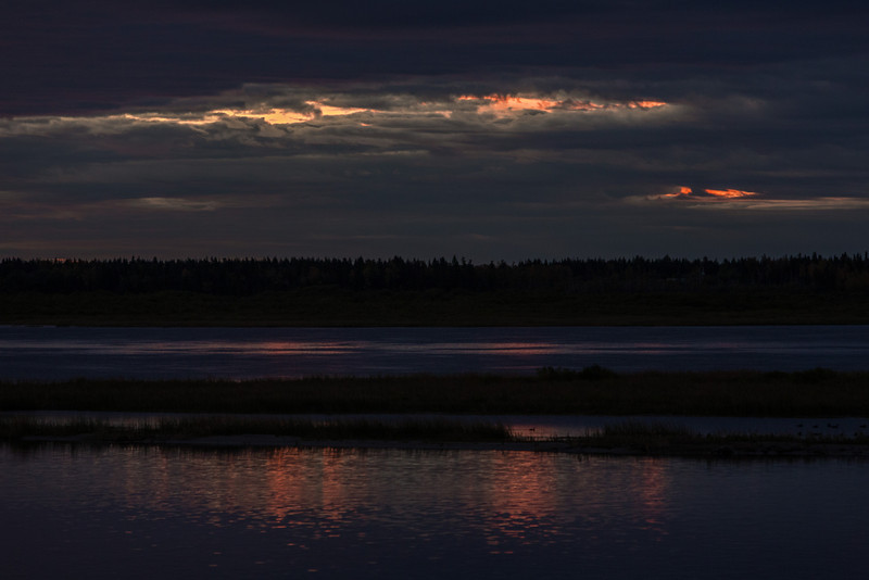 Sky before sunrise over the Moose River at Moosonee. Patches of colour reflected in the river.