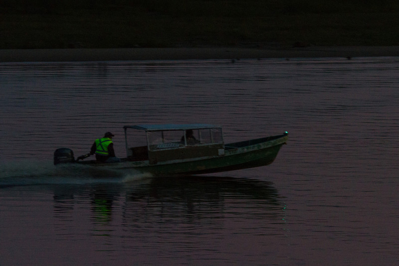 Taxi boat heading up the Moose River after sunset in Moosonee.
