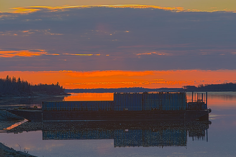 After sunrise at Moosonee, sun heads into the clouds over barges anchored on the Moose River. HDR shot from three exposures; photorealistic.