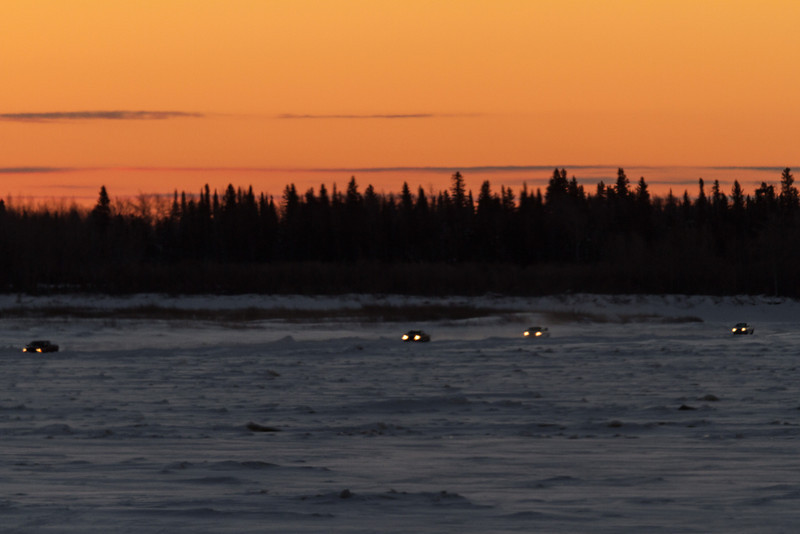Looking across the Moose River from Moosonee around sunrise. Traffic on the river road.