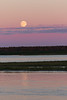 Rising moon above thin clouds across the Moose River from Moosonee.