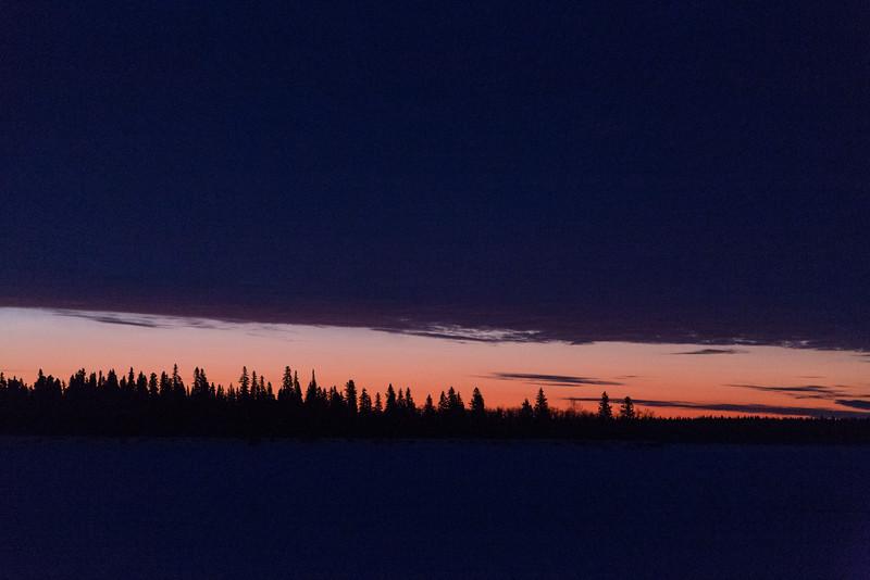 Sky before sunrise looking across the Moose River at Moosonee. Thin wedge of light under dark clouds.