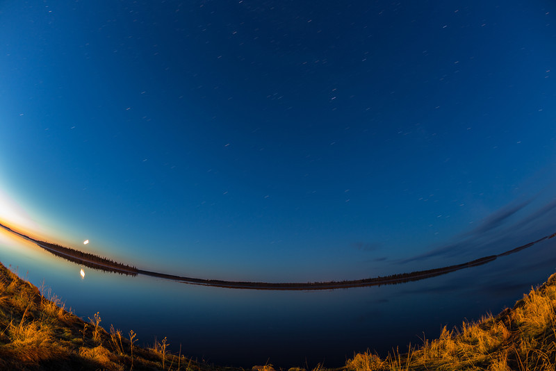 Looking across the Moose River from Moosonee at night. Moon rising over Butler Island and reflected in the river.