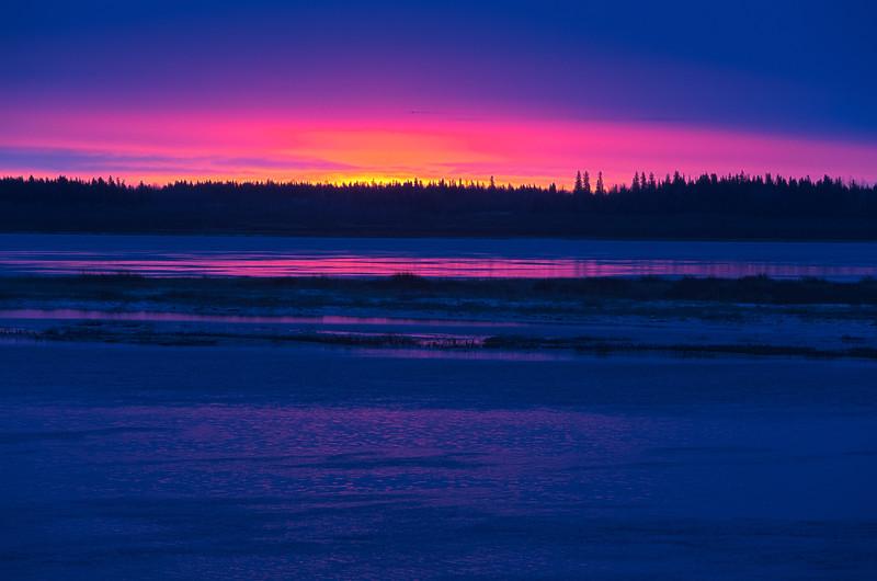 Looking across the Moose River at Moosonee before sunrise. Streak of red along the horizon. HDR Pro.