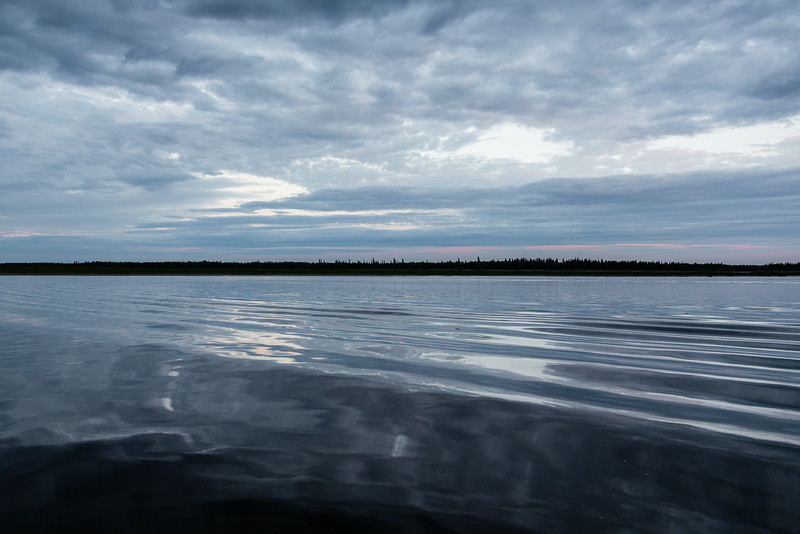 Reflection of clouds in the Moose River at Moosonee. Surface disturbed by passing taxi boat.