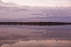 Looking across the Moose River at sunrise at Moosonee. Clouds reflected in the river. Enhanced colours.