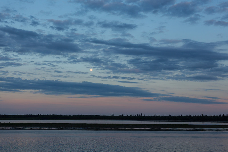Clouds over the Moose River around sunset. Moon emerges from the clouds.