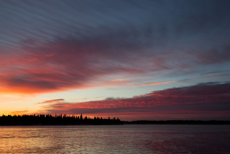 Butler Island, across the Moose River from Moosonee, before sunrise. Coloured clouds reflected in the water. Wider view.