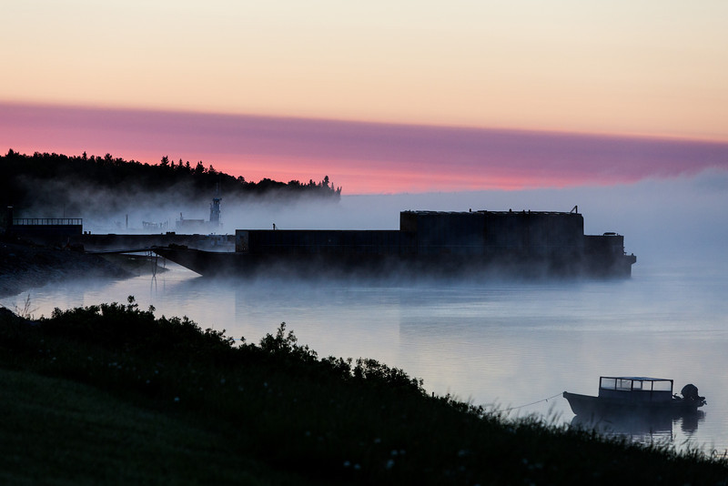 Looking down the Moose River before sunrise on a foggy morning. Canoe and barges.