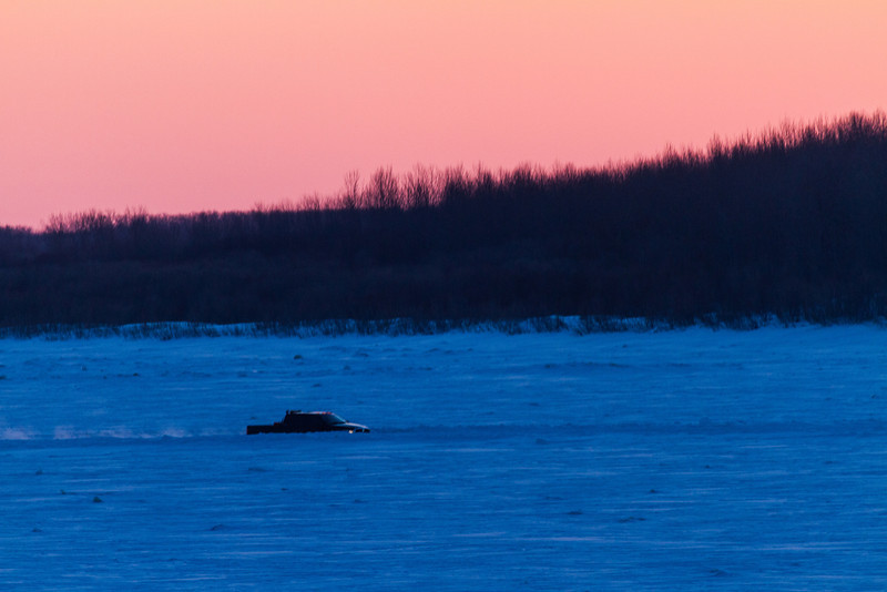 Looking down the Moose River before sunrise. Sky in this direction much redder. Vehicle on winter road.