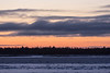 Looking across the Moose River before sunrise from Moosonee. At least four birds high above the clouds.