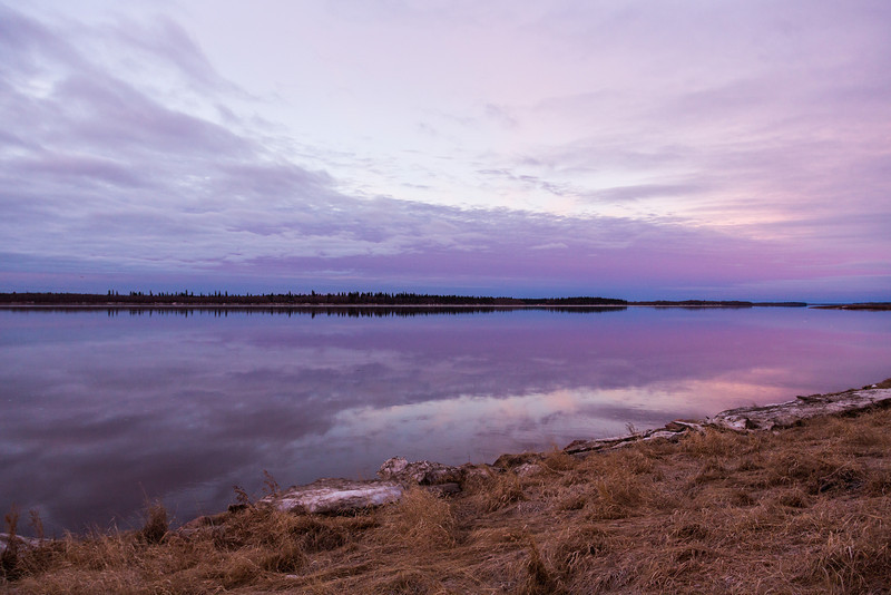 Moose River at Moosonee. Looking upstream just before sunrise. Clouds reflected in the river.