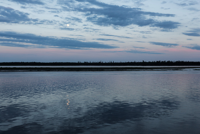 Clouds over the Moose River around sunset. Moon reflected in the water.