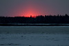 Just a small patch of colour in the sky marks sunrise above the Moose River across from Moosonee.