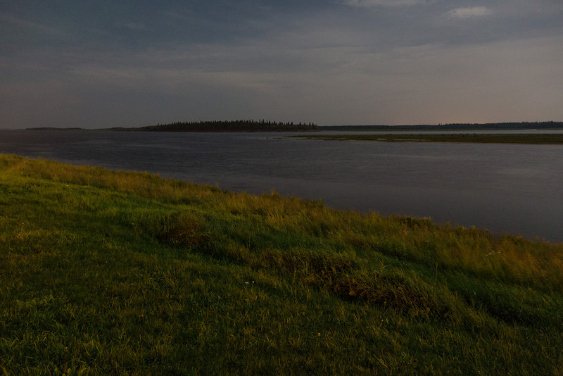 Looking across the Moose River at night under a full moon.