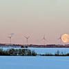 Moon setting behind windmills.