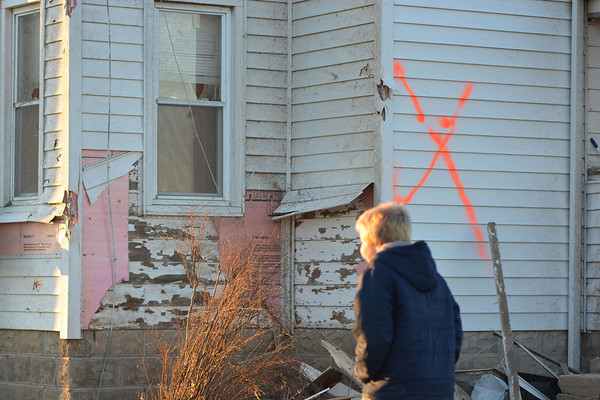 Zain Miller walks around his home, now ruled uninhabitable after Sunday's tornado.