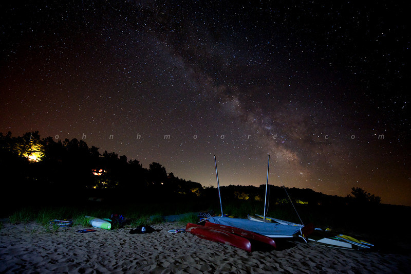 Milky Way over the beach with Sunfish sailboats and kayaks in the foreground.