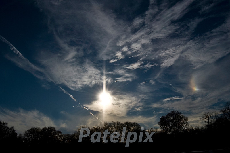 Parhelion, also called sun dogs, are bright colored spots of light to the right or left of the sun occuring due to ice crystals in the atmosphere acting as prisms.  The spots are always at the same elevation as the sun, and usually seen when the sun is at a low angle.  If the crystals are widely scattered, a halo may be seen around the sun.<br /> This photograph was taken from the parking lot at Valley Hospital, Ridgewood, New Jersey in November, 2009.
