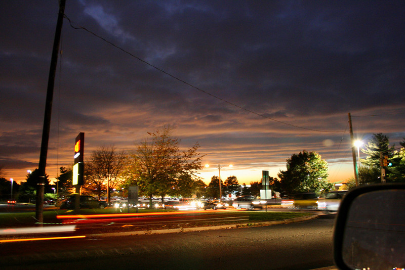 """11/2 Late Night Sunset I took this picture on my way back from Taco Bell while I was waiting in traffic.  The sun was just about done setting, but I managed to capture some of the last colors left in the sky.  I thought it came out pretty well for a handheld shot out the window of my truck.  I particularly like the fact that the streaks from the moving car on the bottom left lined up.  The tail lights stop right where the headlights started. Sorry I lied in the caption yesterday.  This isn't a """"guess what it is"""" picture, unless you want to guess what the signs on the left say.  I can't promise one for tomorrow, but I'll try.  Stay Tuned."""