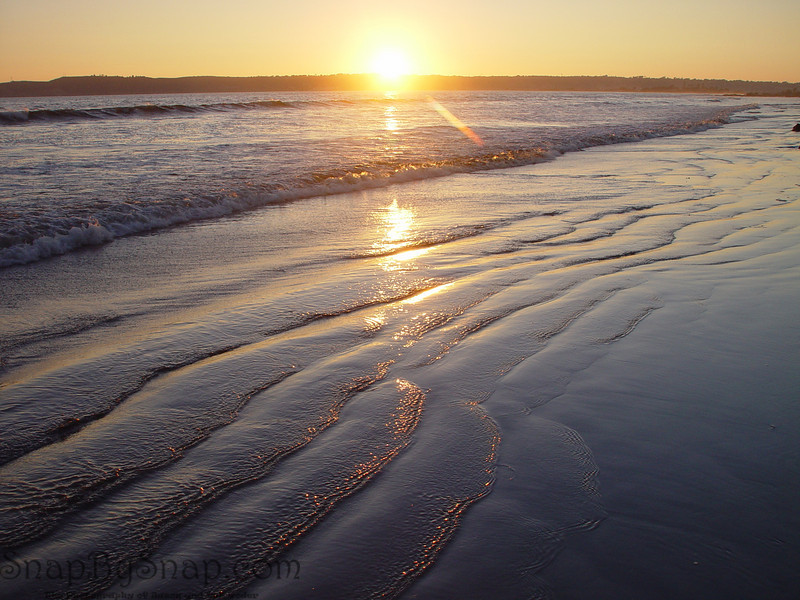 The sun settings over the pacific as viewed from the beach of Coronado Island.